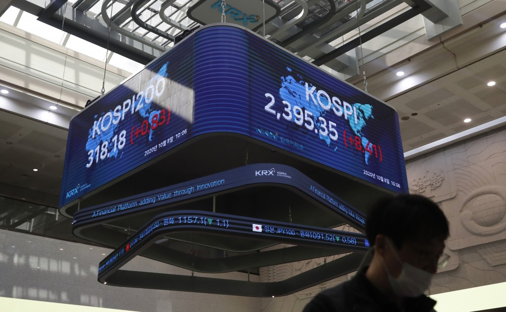 A man wearing a face mask walks near a screen showing the Korea Composite Stock Price Index (KOSPI) at the Korea Exchange in Seoul, South Korea, Thurs...