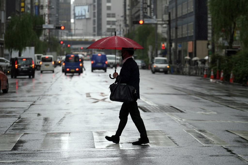 A man walks a pedestrian crossing in the rain Thursday, Oct. 8, 2020, in Tokyo. Typhoon Chan-hom is approaching Japan's main island with authorities w...