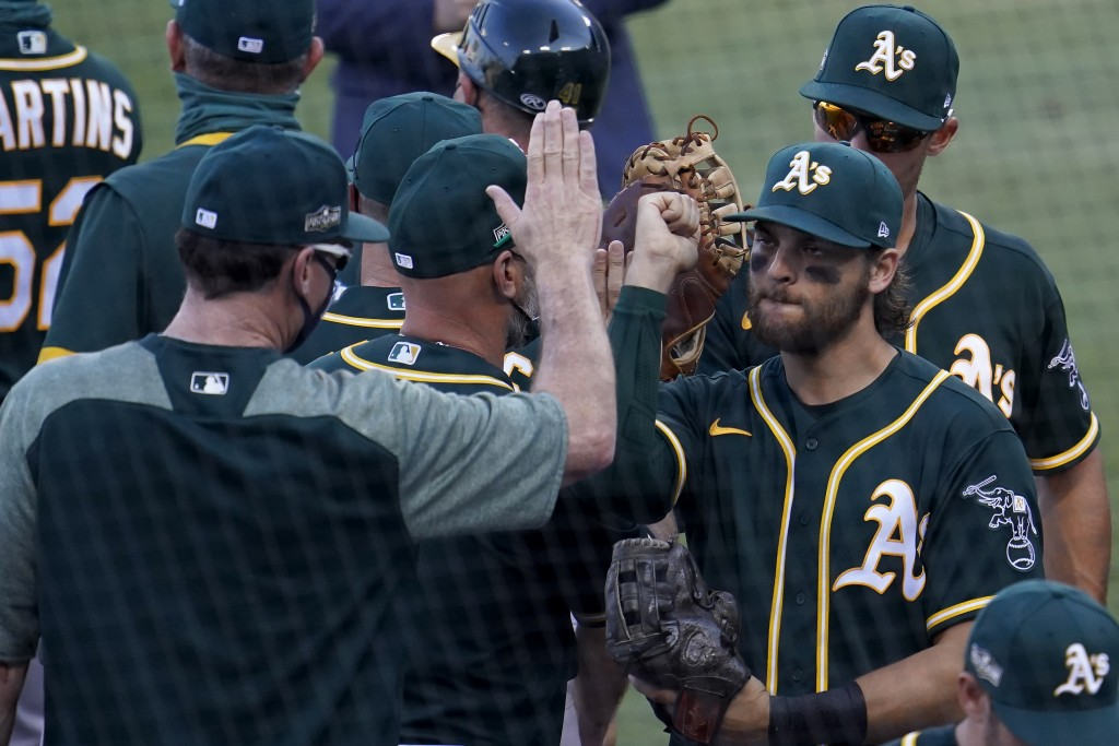 Oakland Athletics' Chad Pinder, right, celebrates with manager Bob Melvin after the Athletics defeated the Houston Astros in Game 3 of a baseball Amer...