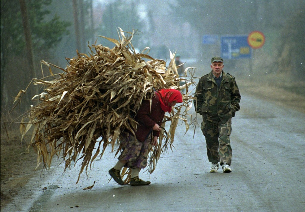 FILE - In this Saturday, Jan 20 1996 file photo, a Bosnian woman carries corn as a Bosnian soldier passes her in Lopare, a Bosnian former frontline vi...