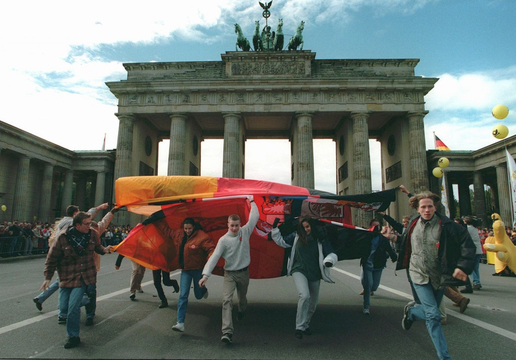 FILE - In this Sunday, Oct. 1, 1995 file photo, youth dance under a giant German flag in front of the Brandenburg Gate in Berlin  during a parade mark...