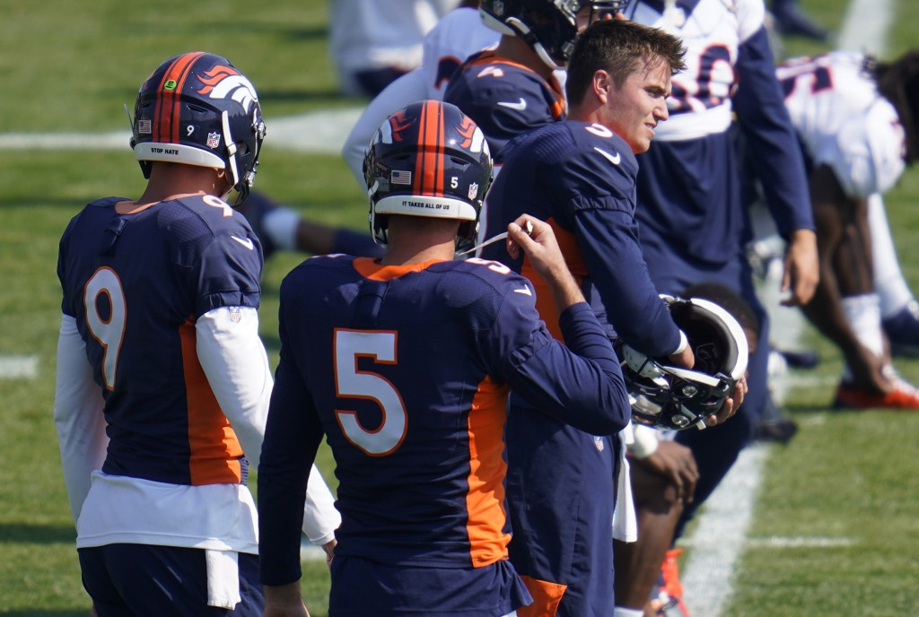 Injured Denver Broncos quarterback Drew Lock (3), right,, puts on his helmet to take part in drills during an NFL football practice at the team's trai...