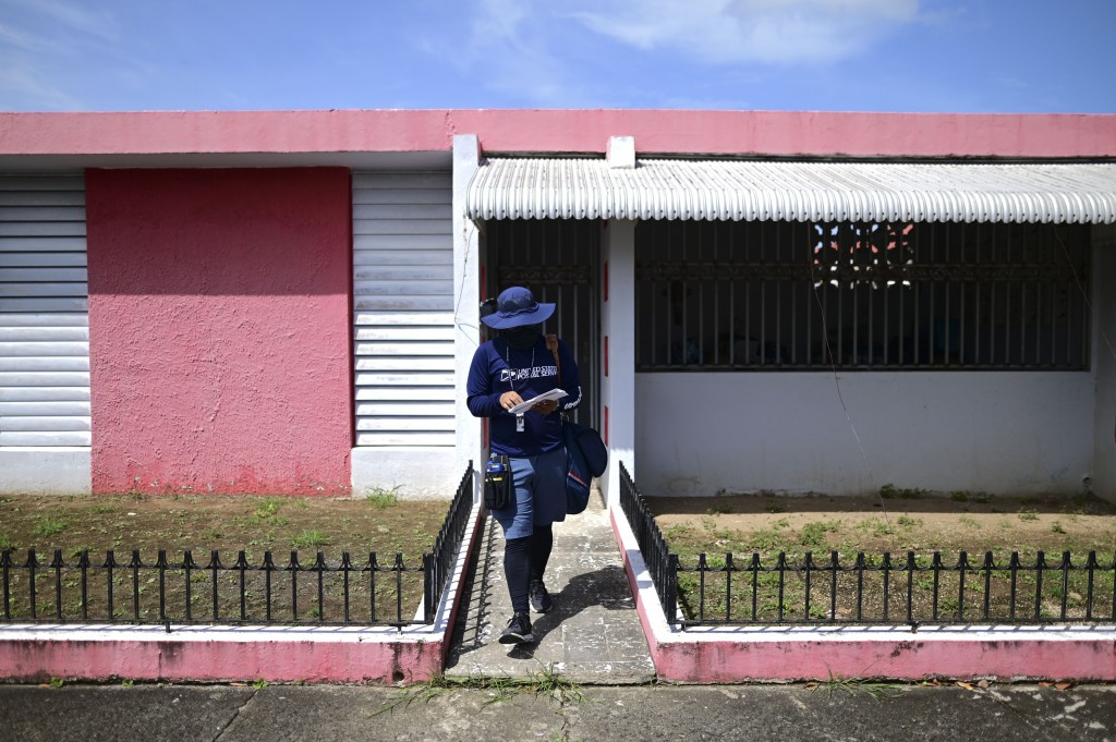 Postal worker Jose Montoya does his rounds in Carolina, Puerto Rico, Thursday, Oct. 1, 2020. More than half of all homes in Puerto Rico lack a physica...