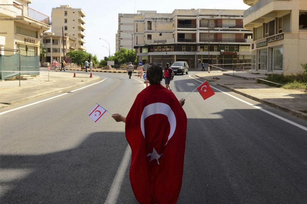 CORRECTS SPELLING OF LOCATION   A woman with Turkish and Turkish Cypriot breakaway flags walks along the new constructed road with abandoned buildings...