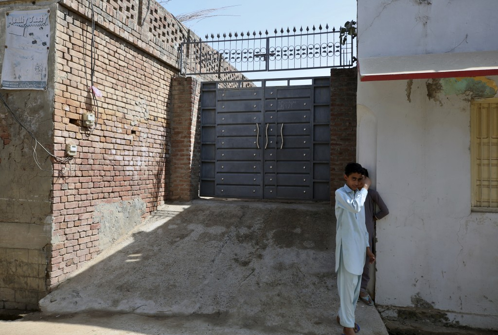 Youngsters stand outside the family house of Ali Hassan, who allegedly attacked two people with a meat cleaver in Paris last month, in Kotli Qazi, Pak...
