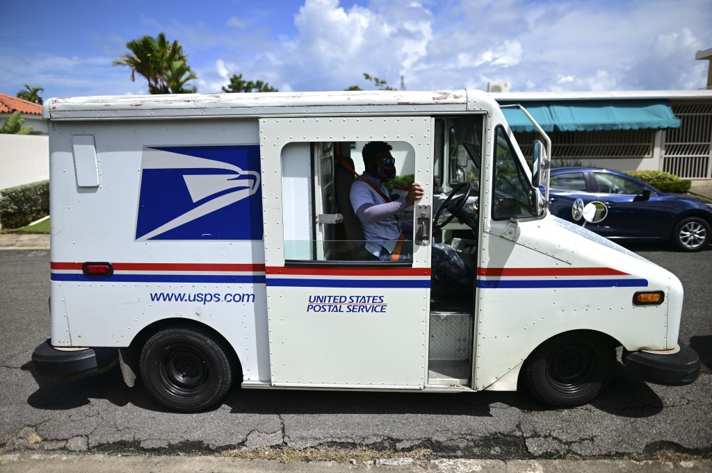 Postal worker Rawy Perez gets in his truck to start his rounds in Carolina, Puerto Rico, Wednesday, Sept. 30, 2020. The absence of street names and nu...