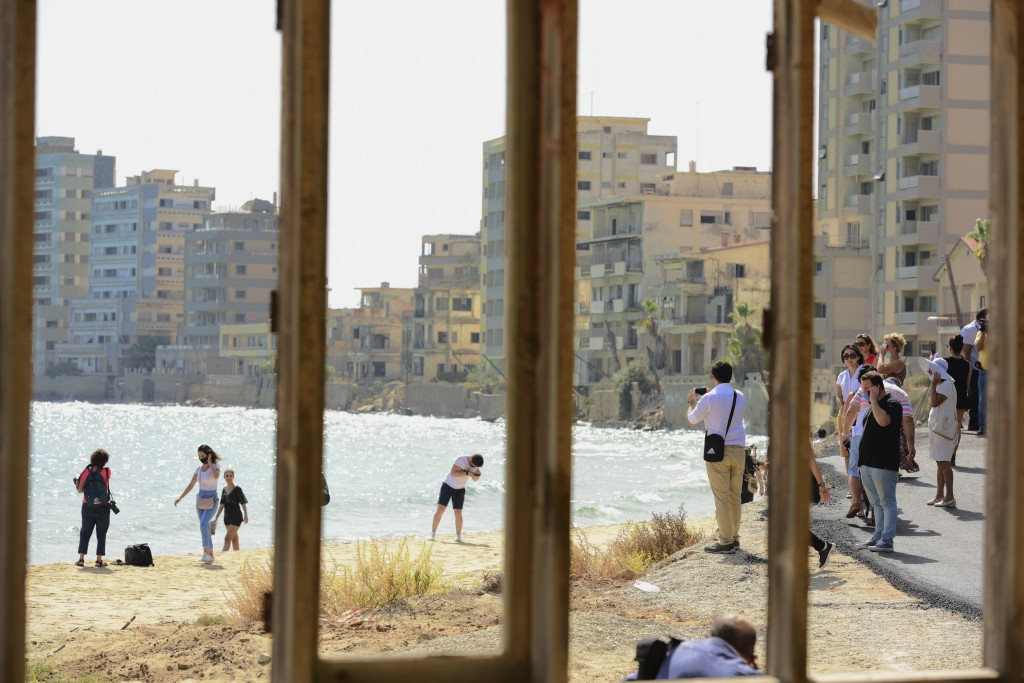 Journalists and public are seen through a window frame at the beach with abandoned hotels, after police open the beachfront of Varosha, an uninhabited...