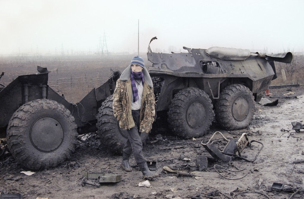 FILE In this Thursday, Jan. 31, 1995 file photo, a Chechen looks towards a Russian checkpoint as he stands in front of the wreckage of a Russian armor...