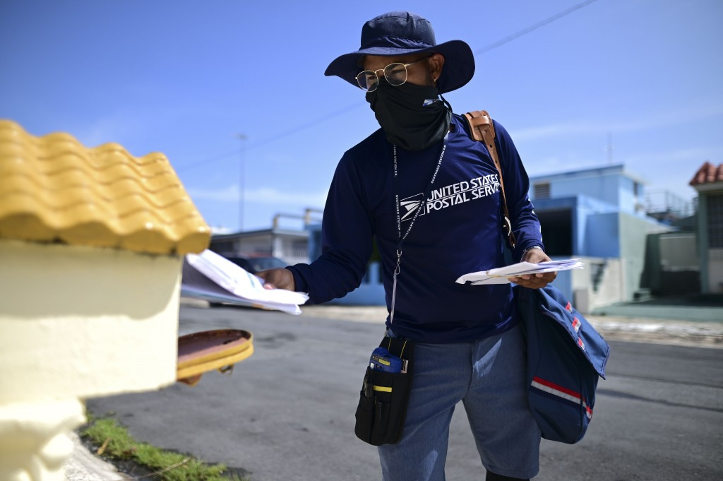 Postal worker Jose Montoya delivers mail in Carolina, Puerto Rico, Thursday, Oct. 1, 2020. More than 300,000 homes across Puerto Rico lack a formal ad...