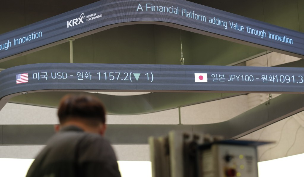 A man stands near a screen showing the foreign exchange rates at the Korea Exchange in Seoul, South Korea, Thursday, Oct. 8, 2020. Asian shares were m...