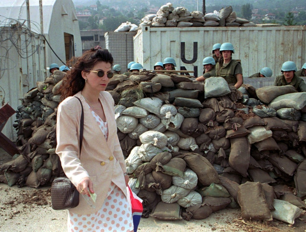 FILE - In this Saturday July 29, 1995 file photo, a Sarajevan woman walks past French United Nations soldiers preparing new barricades at a U.N. compo...