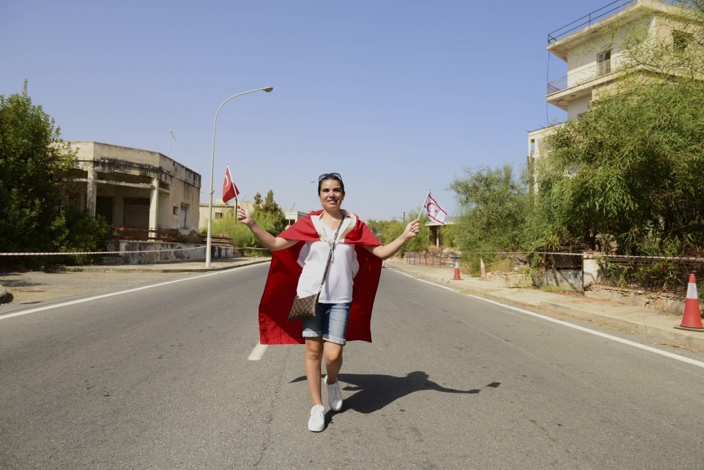 CORRECTS SPELLING OF LOCATION   A woman with Turkish and Turkish Cypriot breakaway flags walks along by abandoned buildings after police open the beac...