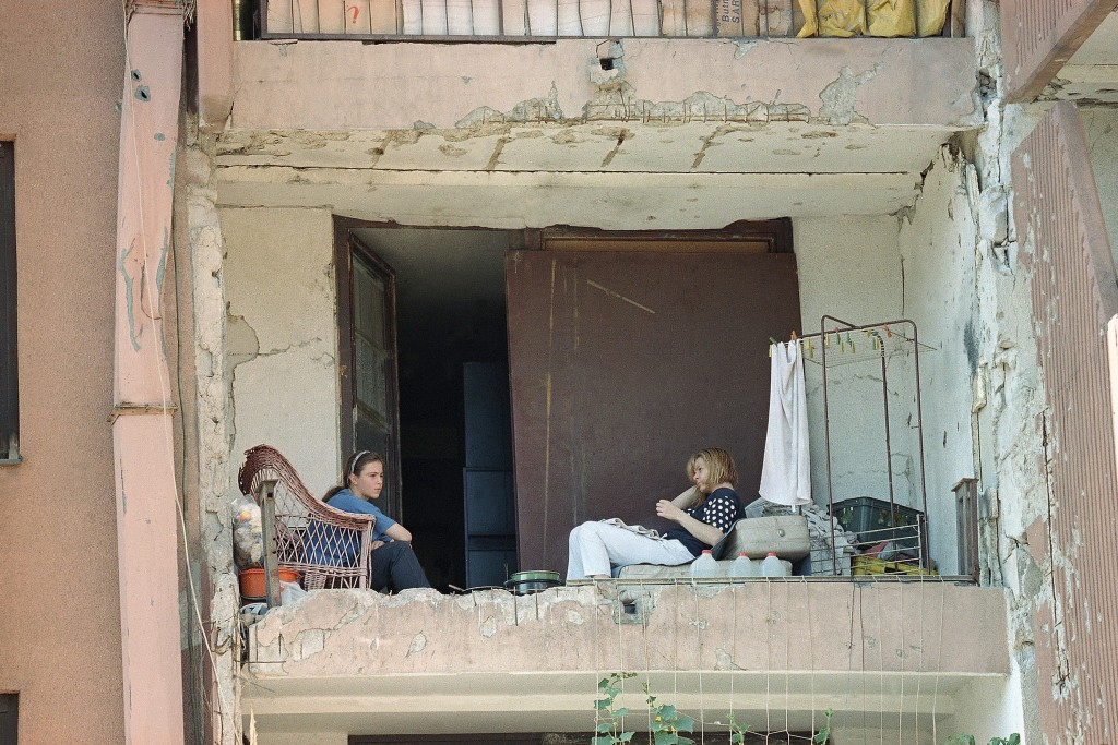 FILE - In this Friday, Aug. 4, 1995 file photo, two women sit on the shattered balcony of their previously destroyed apartment in Sarajevo's outskirts...