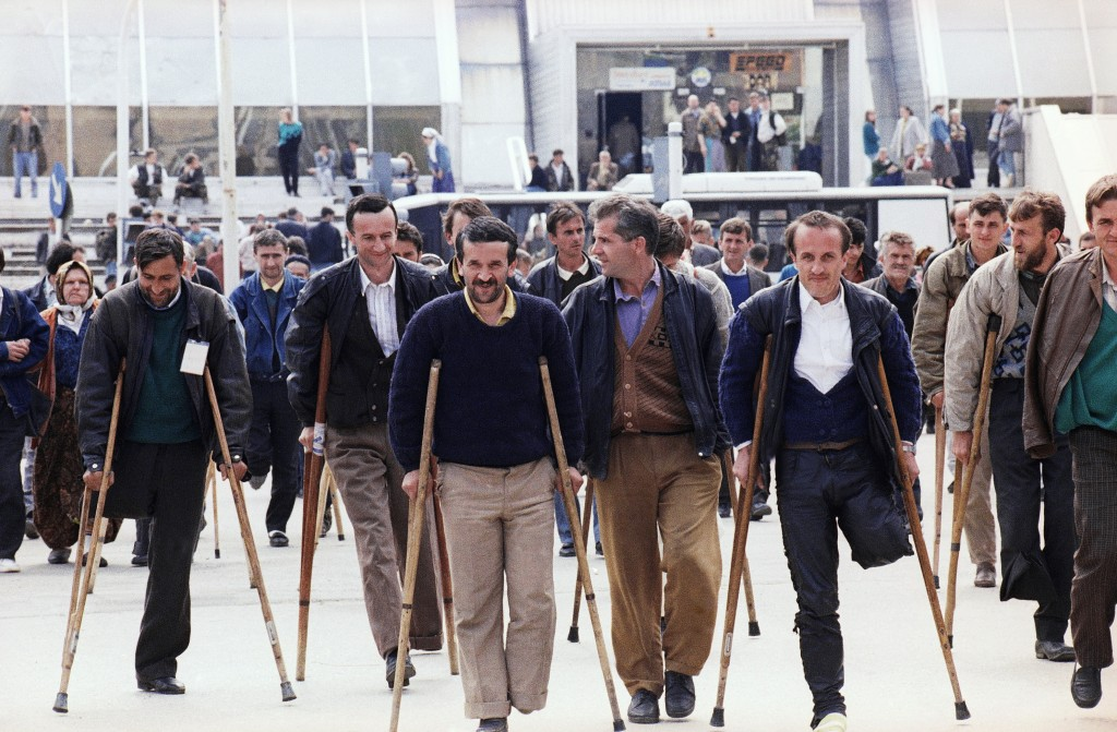 FILE - In this April 20, 1993 file photo refugees of Srebrenica, evacuated a day before by U.N. helicopter, walk with their crutches to a nearby hospi...