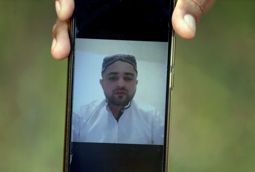 A villager displays a picture of Ali Hassan, a suspect in an attack on two people with a meat cleaver in Paris last month, in his native village of Ko...