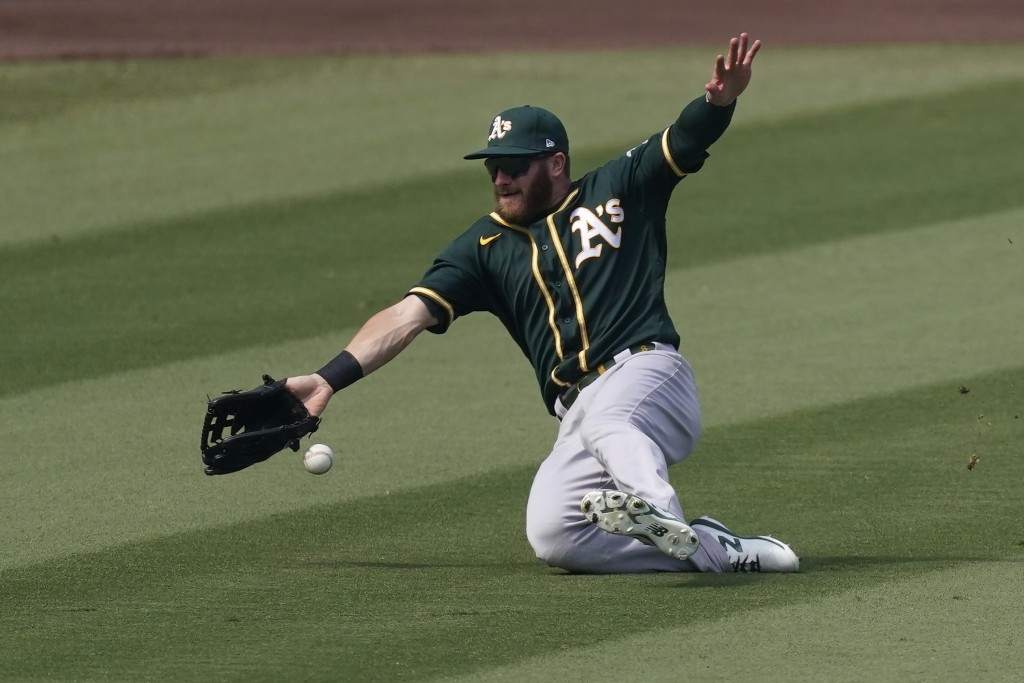 Oakland Athletics left fielder Robbie Grossman cannot catch a base hit by Houston Astros' Josh Reddick during the fourth inning of Game 4 of a basebal...