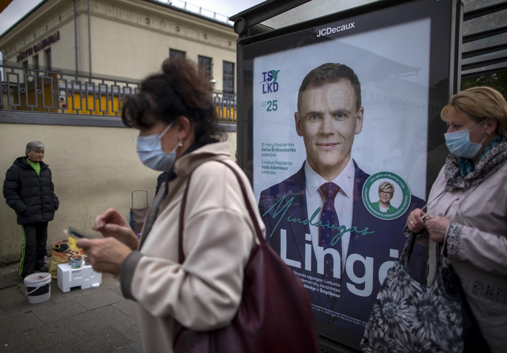 Women wearing face masks to protect against coronavirus wait at a bus stop, with a poster displaying Lithuania's Homeland Union – Christian Democrats ...