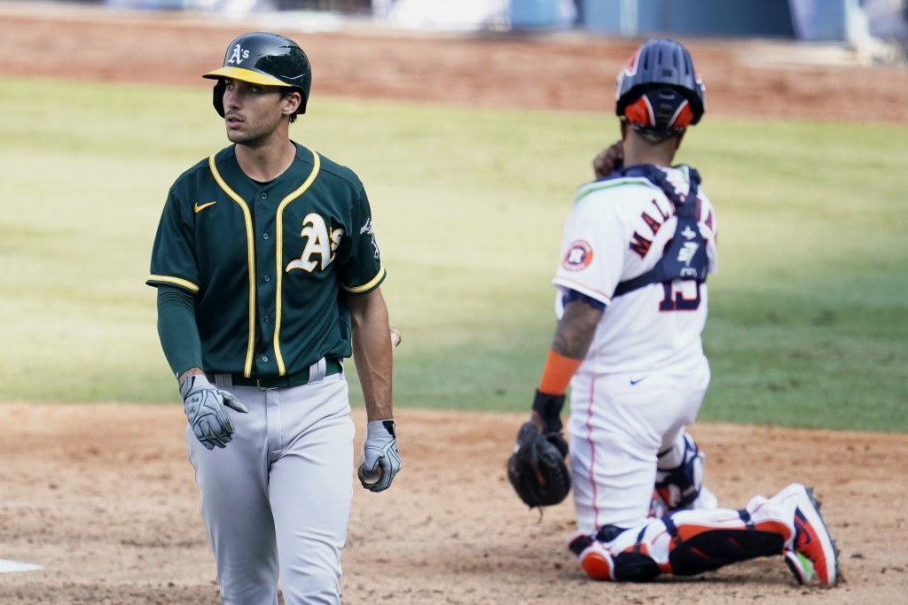 Oakland Athletics' Matt Olson, left, walks to the dugout after striking out against the Houston Astros during the eighth inning of Game 4 of a basebal...