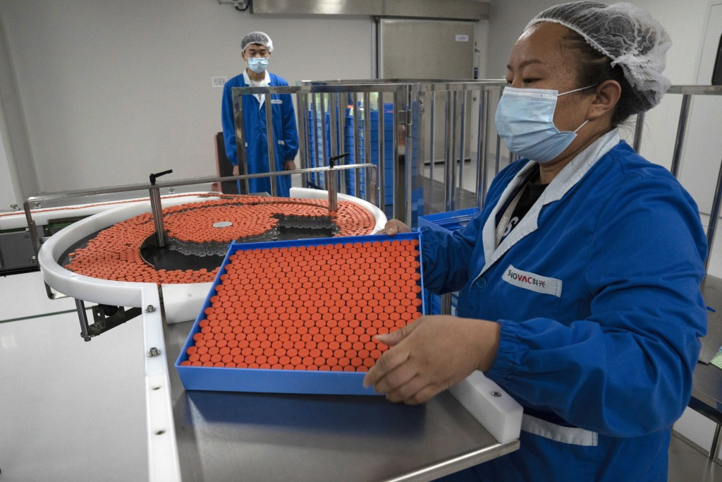 FILE - In this Sept. 24, 2020, file photo, a worker feeds vials for production of SARS CoV-2 Vaccine for COVID-19 at the SinoVac vaccine factory in Be...