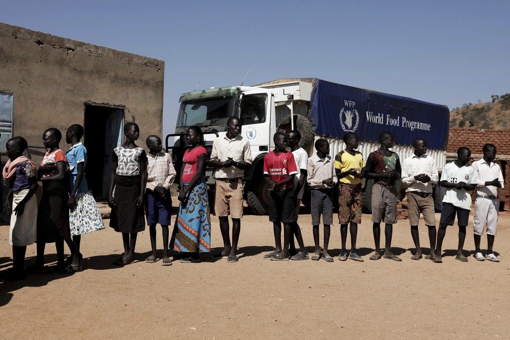 FILE - In this Jan. 9, 2020 file photo, children wait in line to receive aid during a visit organized by The World Food Program (WFP) at Koge School, ...
