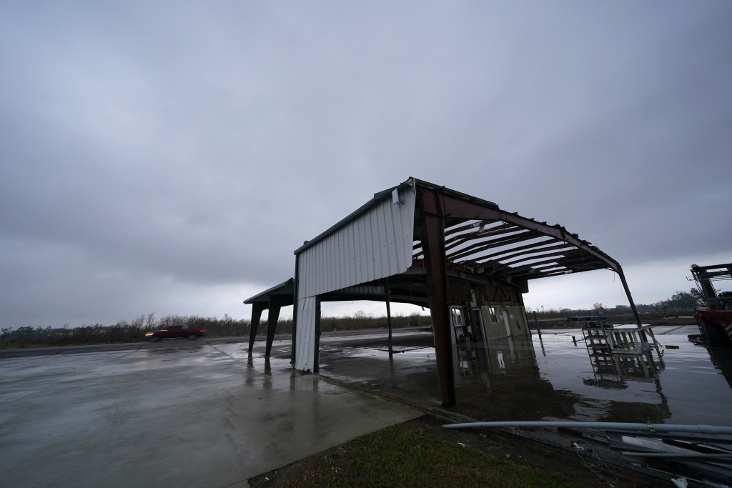 A car leaves Cameron, La., Thursday, Oct. 8, 2020, past a building destroyed by Hurricane Laura, in advance of Hurricane Delta, expected to make landf...