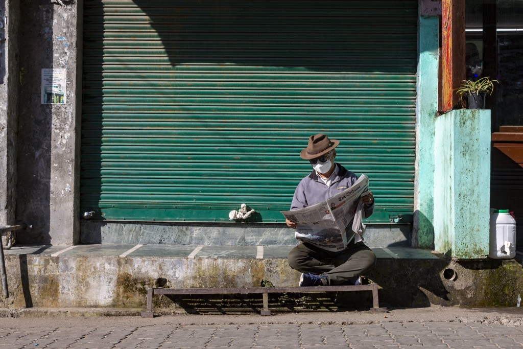 A man wearing a mask to protect himself from the coronavirus reads a newspaper in front of a closed shop in Dharmsala, India, Friday, Oct. 9, 2020. In...