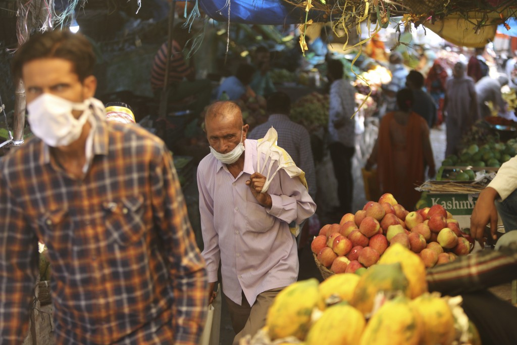 Indians wearing face masks as a precaution against the coronavirus walk in a market area in Jammu, India, Friday, Oct. 9, 2020. India is the world's s...