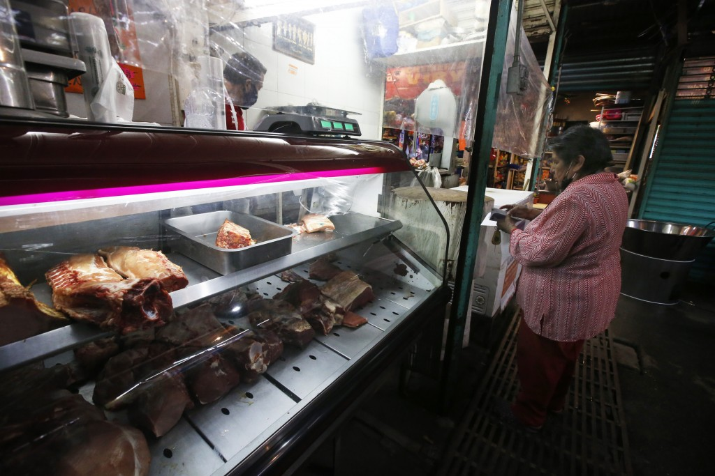Josefina Rodriguez uses coupons provided by the municipality of Iztapalapa to buy meat at a corner shop in Iztapalapa, Mexico City, Thursday, Oct. 8, ...