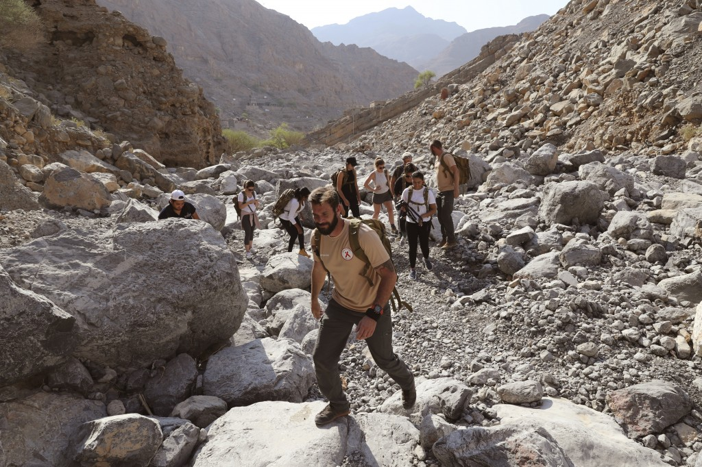 Martin Norton, lead instructor of the Bear Grylls Survival Academy, centre front, leads the group during a survival trial at the Jebel Jais, about 30 ...