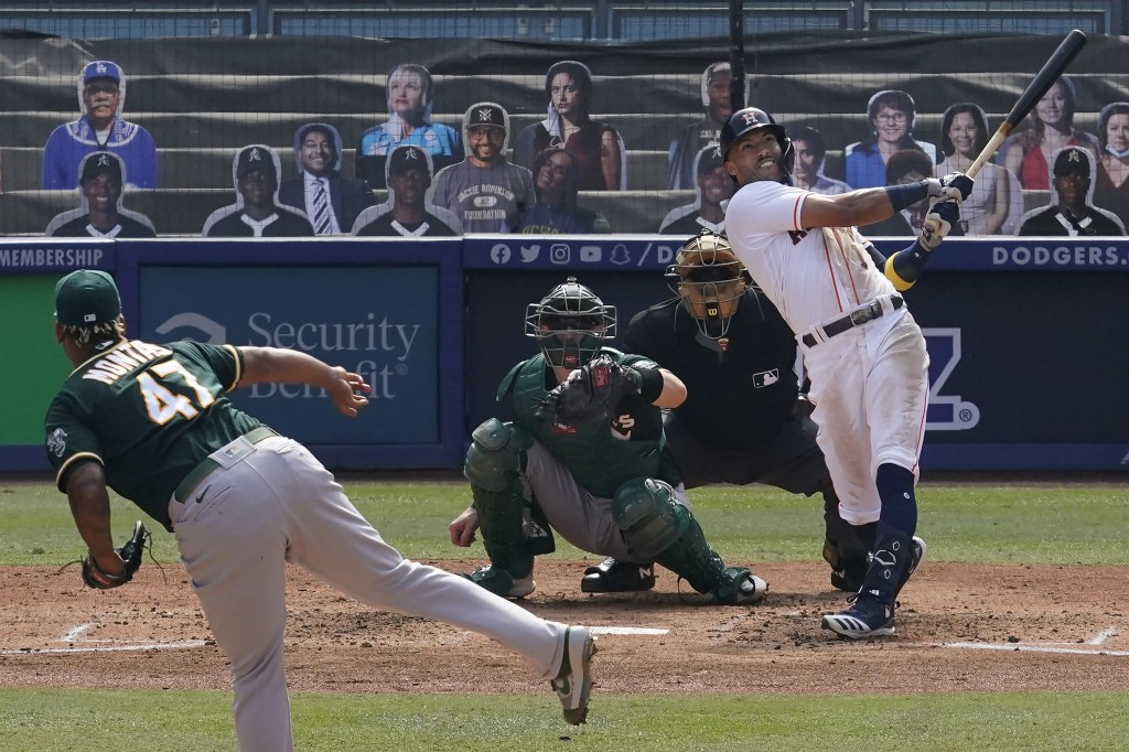 Houston Astros' Carlos Correa, right, hits a three-run home run off of Oakland Athletics pitcher Frankie Montas, left, during the fourth inning of Gam...
