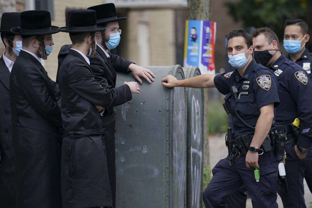Members of the Orthodox Jewish community speak with NYPD officers, Wednesday, Oct. 7, 2020, in the Borough Park neighborhood of the Brooklyn borough o...