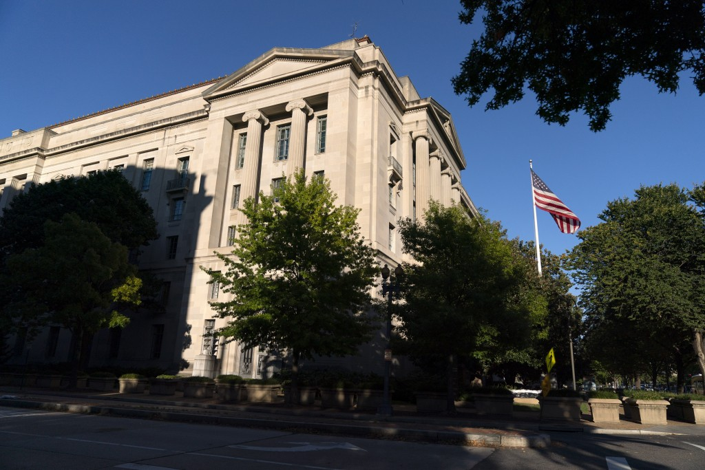 The American flag flies outside of the Justice Department building, Thursday, Oct. 8, 2020, in Washington. (AP Photo/Jacquelyn Martin)