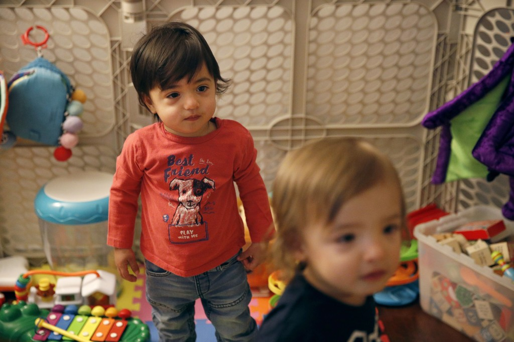 FILE - This Jan. 23, 2018, file photo shows 16-month-old Ethan Dvash-Banks, left, and his twin brother, Aiden, playing in the living room of their apa...