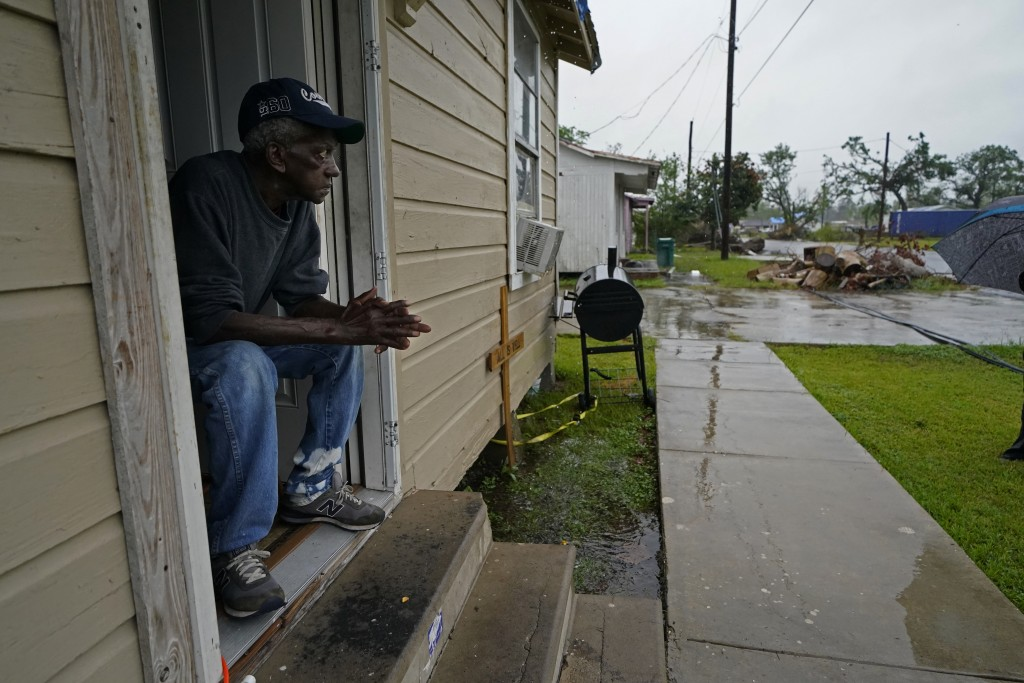 Ernest Jack, whose home was severely damaged from Hurricane Laura, sits in his front doorway as he waits for the arrival of Hurricane Delta expected t...