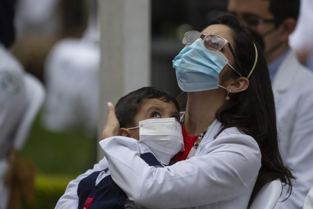A health worker at the San Juan de Dios hospital holds a child during a minute of silence in memory of her colleagues who have fallen victim to COVID-...