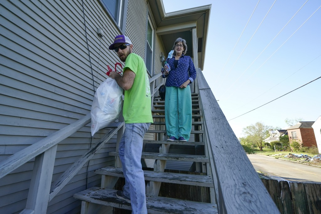 Caleb Cormier speaks with Jo Lynne Southerland, after Hurricane Delta moved through, Saturday, Oct. 10, 2020, in Lake Charles, La. Delta hit as a Cate...
