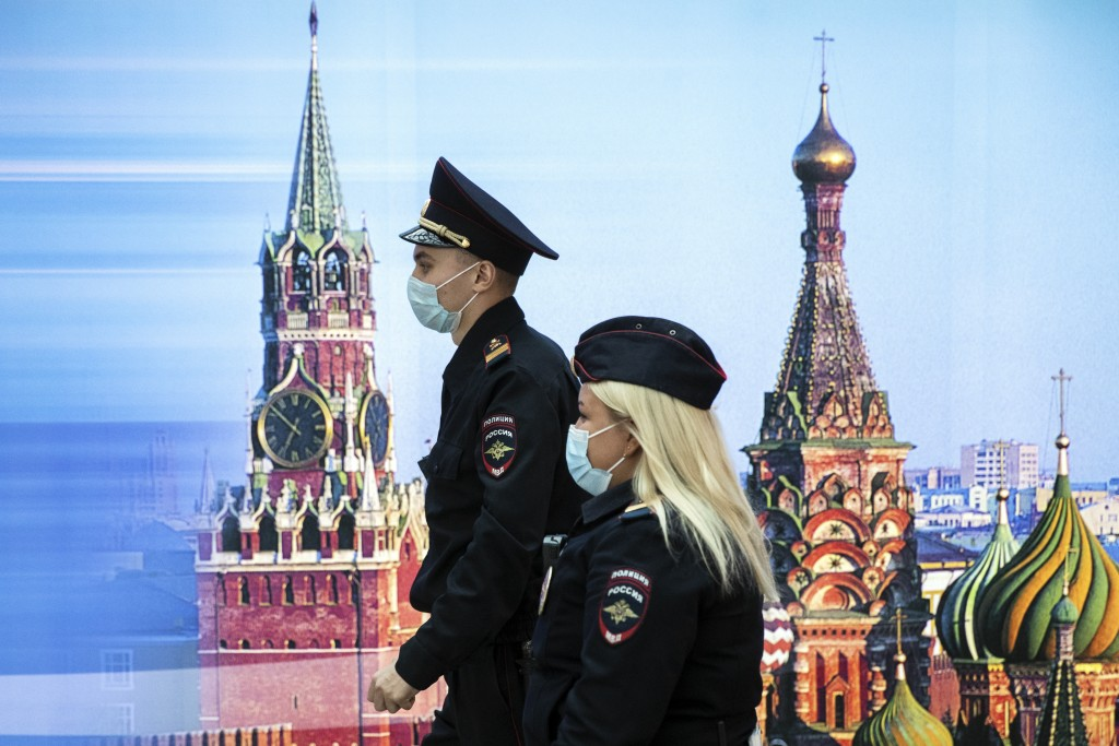 Police officers wearing face masks to protect against coronavirus walk past a photo of Kremlin's Spasskaya Tower, left, and St. Basil's Cathedral in S...