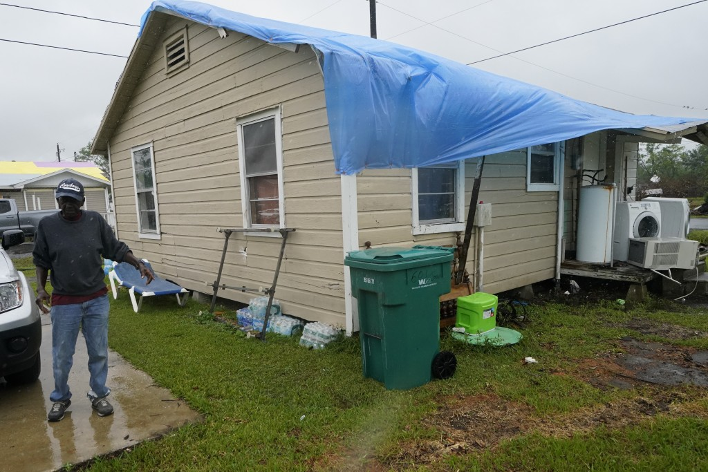 Ernest Jack moves near his home that was hit by Hurricane Laura ahead of Hurricane Delta, Friday, Oct. 9, 2020, in Lake Charles, La. Forecasters said ...