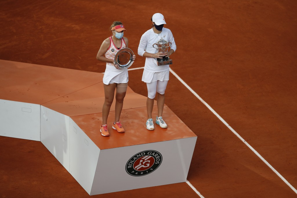 Poland's Iga Swiatek, right, holds the trophy after winning the final match of the French Open tennis tournament against Sofia Kenin of the U.S., left...