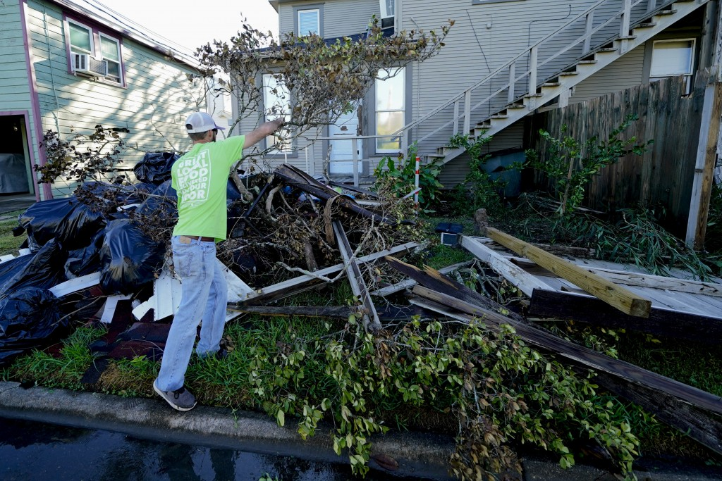 Caleb Cormier moves debris after Hurricane Delta moved through, Saturday, Oct. 10, 2020, in Lake Charles, La. Delta hit as a Category 2 hurricane with...