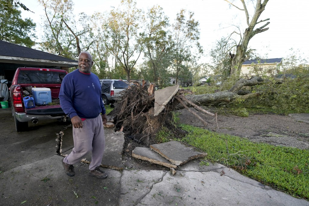 Marcus Peterson walks past a downed tree in his yard after Hurricane Delta moved through, Saturday, Oct. 10, 2020, in Jennings, La. Delta hit as a Cat...