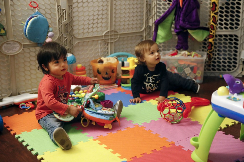 FILE - In this Jan. 23, 2018, file photo, 16-month-old Ethan Dvash-Banks, left, and his twin brother Aiden play in the living room of their apartment ...