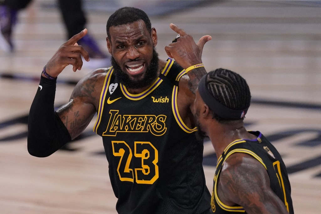 Los Angeles Lakers forward LeBron James talks with guard Kentavious Caldwell-Pope during the first half in Game 5 of basketball's NBA Finals against t...