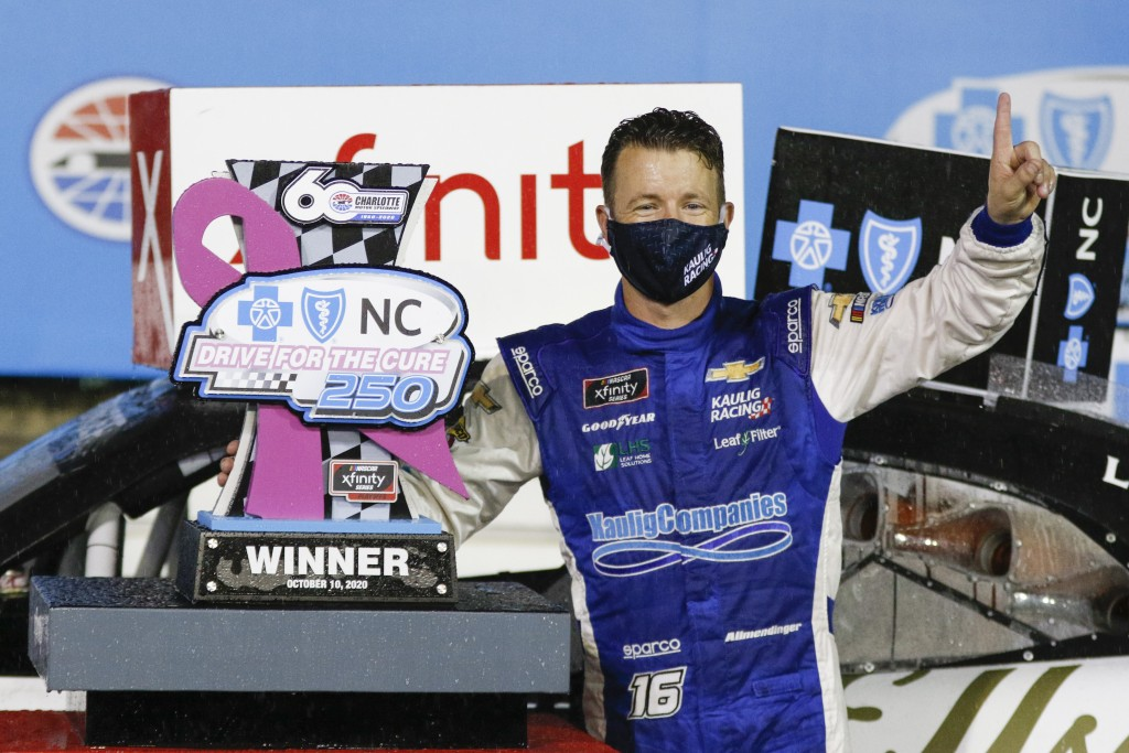 AJ Allmendinger stands beside his trophy after winning a NASCAR Xfinity Series auto race at Charlotte Motor Speedway in Concord, N.C., Saturday, Oct. ...