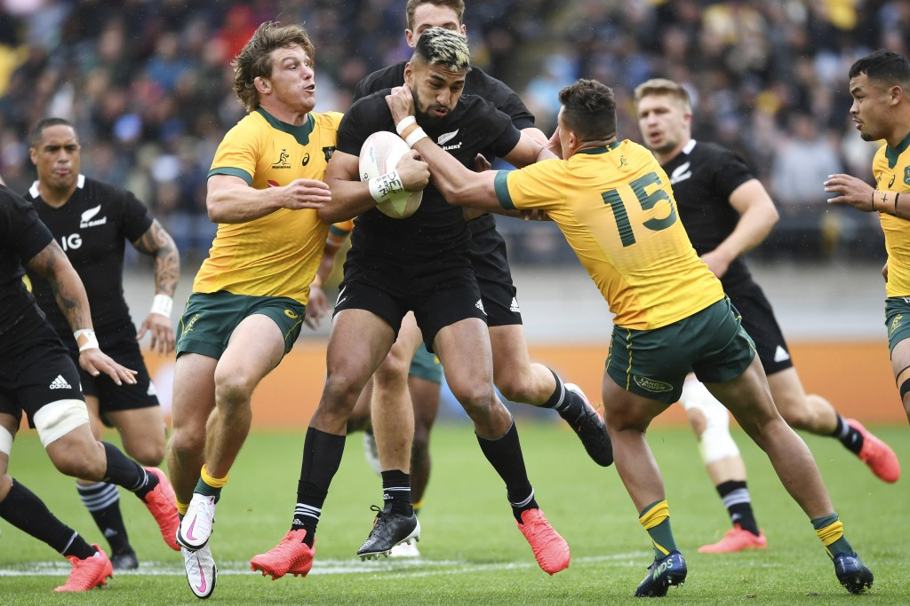 New Zealand's Rieko Ioane is tackled by Australia's Michael Hooper, left, and Tom Banks, right, during the Bledisloe Cup rugby game between the All Bl...