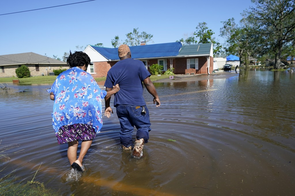 Soncia King holds onto her husband Patrick King in Lake Charles, La., Saturday, Oct. 10, 2020, as they walk through the flooded street to their home, ...