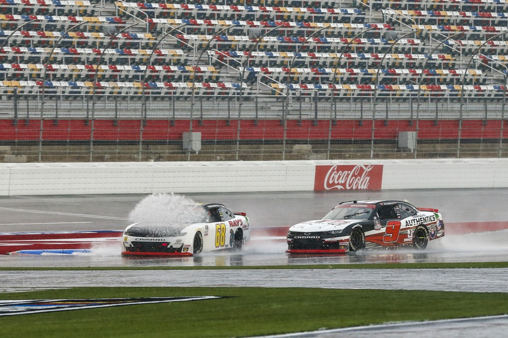 Brandon Brown (68) hits a puddle in front of Noah Gragson (9) during a NASCAR Xfinity Series auto race at Charlotte Motor Speedway in Concord, N.C., S...
