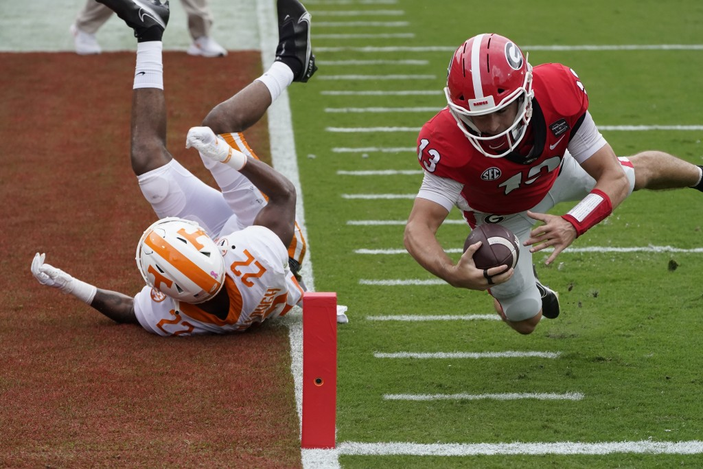 Georgia quarterback Stetson Bennett (13) dives past Tennessee defensive back Jaylen McCollough (22) to score a touchdown in the first half of an NCAA ...