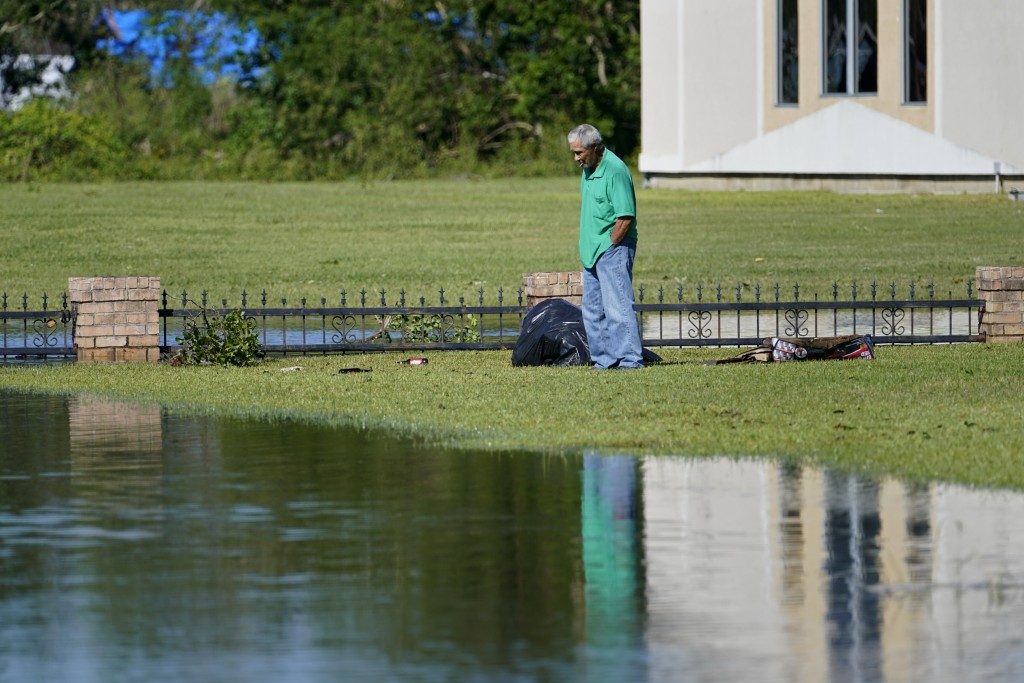 A man stands on his front lawn and looks at the flooded street in Lake Charles, La., Saturday, Oct. 10, 2020, after Hurricane Delta moved through on F...