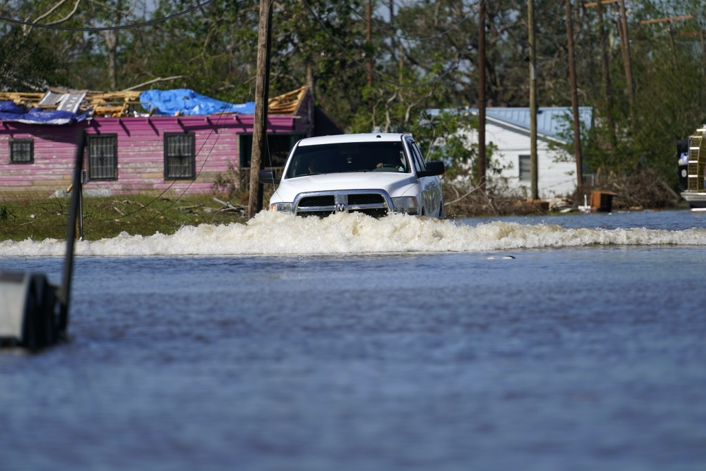 A truck drives through a flooded street in Lake Charles, La., Saturday, Oct. 10, 2020, past a home with damage from Hurricane Laura, after Hurricane D...